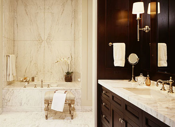 Elegant bathroom with bookmatched marble stone and wood panelled vanity
